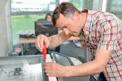 修理办公用打印机的杂物工 免版税库存图片
