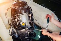 修理可膨胀的汽艇引擎的技工在小船车库 船引擎季节性服务和维护 船马达与 免版税库存照片