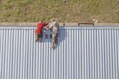 修理商店屋顶的工作者 免版税库存照片