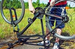 修理在一个象草的领域的人的胳膊一辆自行车。 库存图片