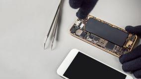 修理在书桌上的技术员残破的智能手机 库存图片