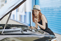 修理在城市街道上的一个白色帽子的年轻美丽的妇女一辆汽车 免版税库存图片