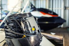 修理在小船车库的可膨胀的汽艇引擎 船引擎季节性服务和维护 有开放盖子的船马达 图库摄影