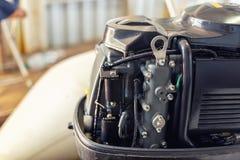 修理在小船车库的可膨胀的汽艇引擎 船引擎季节性服务和维护 有开放盖子的船马达 库存照片