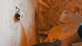 修理在房子里 剥去从墙壁的老棕色墙纸 老墙纸一个大片断剥落墙壁 股票录像