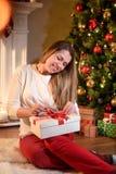 修理在新年礼物盒微笑的女孩一条丝带 免版税库存照片