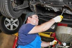 修理在服务站的汽车修理工安装工一辆汽车 免版税库存图片
