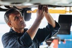 修理在服务站的汽车机械师一辆汽车 图库摄影