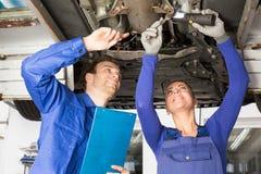 修理在水力舷梯的机械工一辆汽车 免版税图库摄影