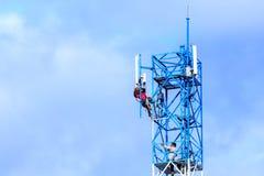 修理在电信塔的技术员 免版税库存图片