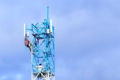 修理在电信塔的技术员 库存图片