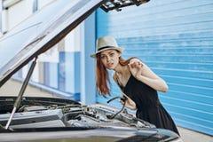 修理在街道,情感上的一个白色帽子的年轻美丽的妇女一辆汽车 库存照片