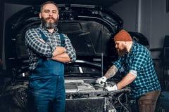 修理在车库的两个人一辆汽车 免版税图库摄影