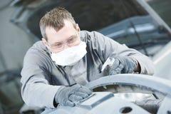 修理在车库的人工作者铺沙的汽车车身 图库摄影
