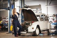 修理在车库的性感的妇女一辆减速火箭的汽车 免版税库存图片
