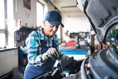 修理在车库的资深女性技工一辆汽车 免版税库存图片