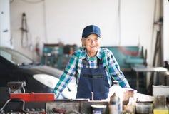 修理在车库的资深女性技工一辆汽车 免版税库存照片