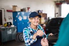 修理在车库的资深女性技工一辆汽车 库存照片