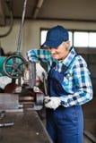 修理在车库的资深女性技工一辆汽车 库存图片