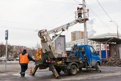 修理在输电线的工作在有混凝土的中心城市在 库存图片