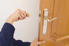 修理在门的木匠一把锁与螺丝刀 库存照片