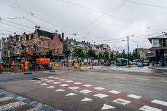 修理在阿姆斯特丹街道的工作者电车轨道每多云和雨天 库存图片