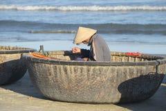 修理在他的小船的渔夫网 岘港市,越南 免版税库存照片