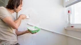 修理墙壁的年轻人在他的公寓,应用在墙壁上的膏药混合 免版税库存图片