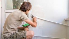 修理墙壁的年轻人在他的公寓,应用在墙壁上的膏药混合 免版税库存照片