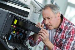 修理大影印机调色剂的老人和技术员 库存图片
