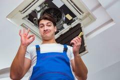 修理天花板空调装置的工作者 库存照片