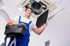 修理天花板空调装置的工作者 免版税库存图片