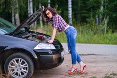 修理她残破的汽车的美丽的少妇在路附近 库存照片