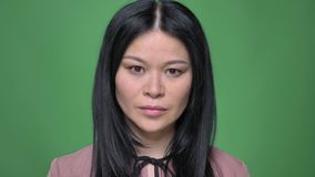 修理她的在照相机前面的年轻可爱的亚裔女性特写镜头射击头发有在绿色隔绝的背景 影视素材