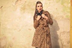 修理她的外套的华美的时尚妇女 库存图片