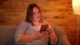 修理她的头发的轻松的正大小模型画象拿着在舒适家庭环境的一个智能手机 影视素材