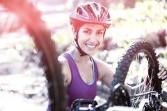 修理她的自行车的女性骑自行车者在公园 免版税库存照片
