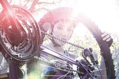 修理她的自行车的女性骑自行车者在公园 库存图片