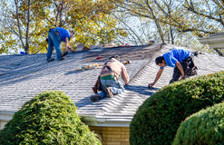 修理家的屋顶的工作者 免版税库存照片
