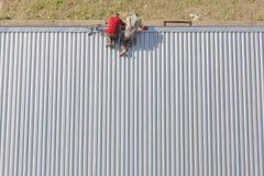 修理屋顶的工作者 免版税库存图片