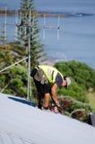 修理屋顶的盖屋顶的人 库存图片