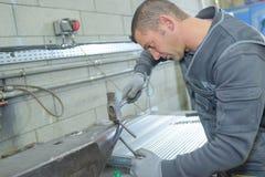 修理工业厨房水槽的水管工 库存照片