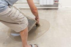 修理工作 倾吐的地板在屋子里 填装冗长的句子地板修理并且装备 在地板上的工作者倾吐的混凝土 库存照片