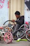 修理微笑的妇女的美好的自行车山维修服务 库存图片