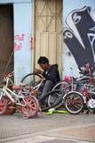 修理微笑的妇女的美好的自行车山维修服务 免版税图库摄影