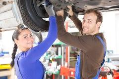 修理在液压悬挂的二位技工一辆汽车 免版税图库摄影