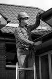 修理房子屋顶的工作者黑白画象 免版税库存照片