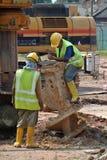 修理打扰堆船具木钻的工作者在建造场所 免版税库存照片