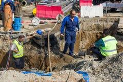 修理打破的总水管的公共乘员组 库存照片