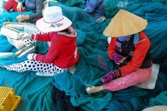 修理捕鱼网的妇女 库存图片